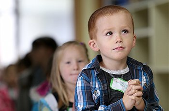 Kindergarten student at Jefferson Lincoln looks up at his teacher